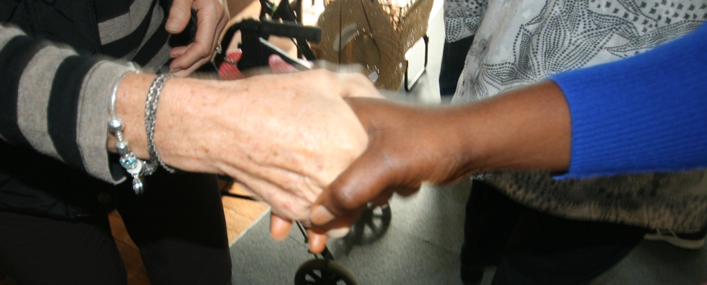 Two hands locked in a handshake during a greeting of the peace in church