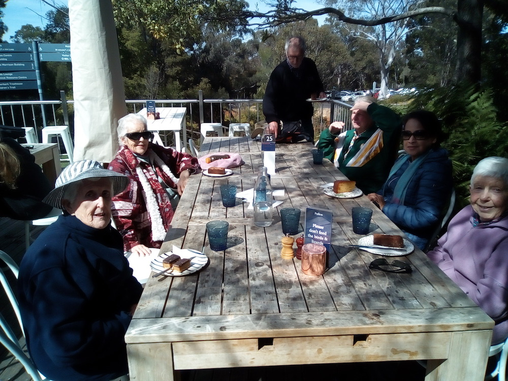 Group sharing morning tea at at an outdoor table in the semi-shade
