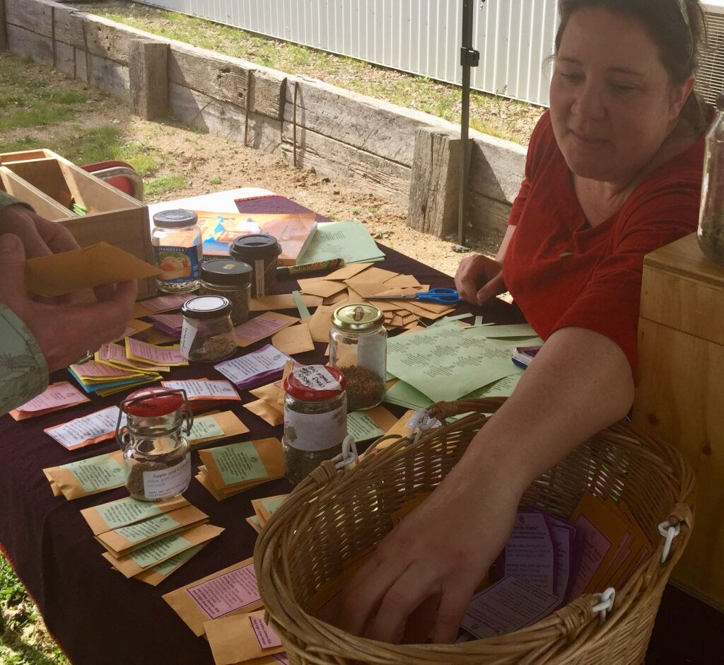 Stall with seed packets and stallholder demonstrating seed sourcing