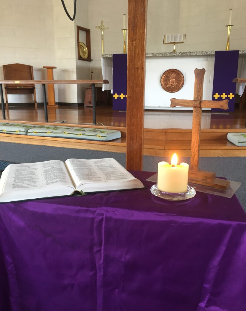 Small table with cross, open Bible and candle, in front of Holy Cross altar